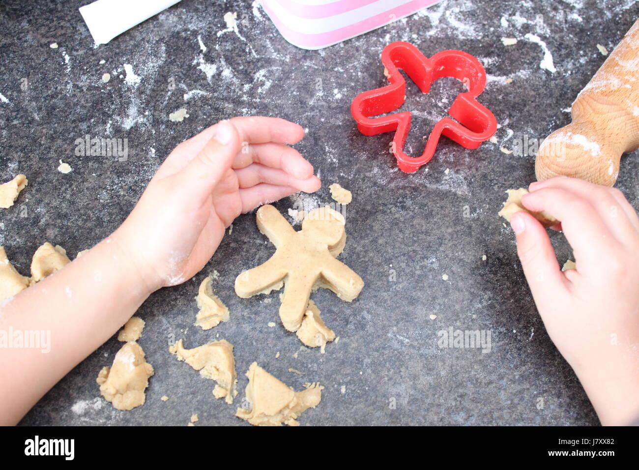 Close up of kids hands making gingerbread men - Stock Image