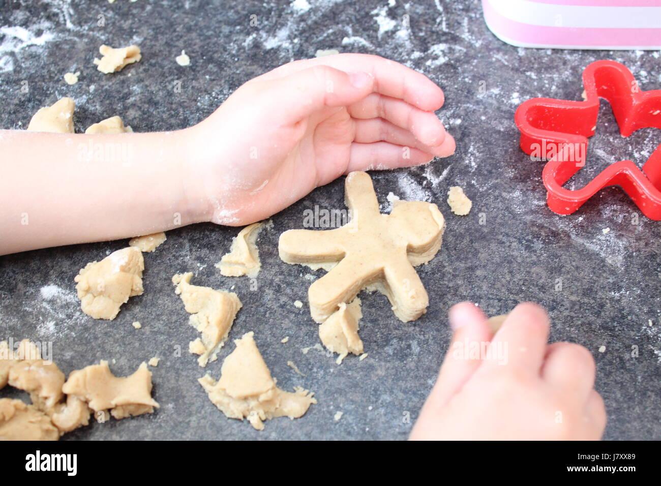 Children's hands making Gingerbread men - Stock Image