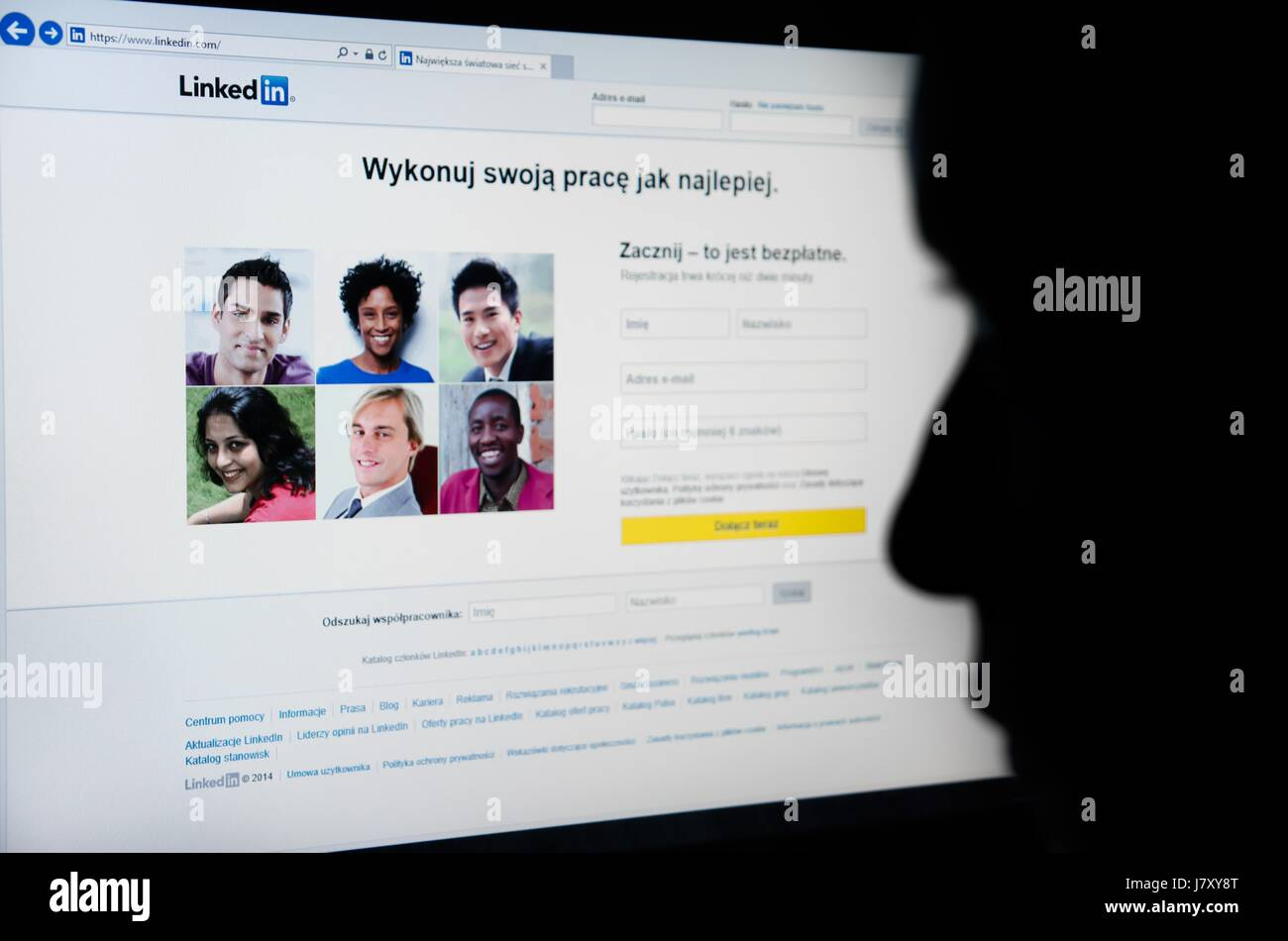 Face looking at Linkedin.com homepage on the screen - business-oriented social networking service - Stock Image