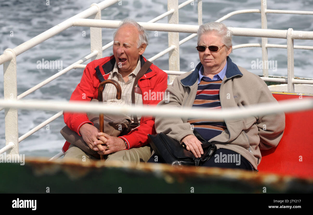 ELDERLY MAN YAWNING WHILST SITTING ON FERRY BOAT WITH ELDERLY LADY COUPLE RE COUPLES OAPS RETIREMENT UK - Stock Image