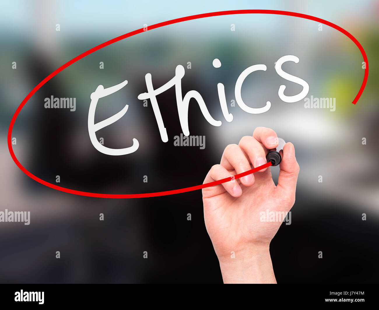 Man hand writing Ethics on visual screen. Business,help, internet, technology concept. Isolated on office. Stock - Stock Image