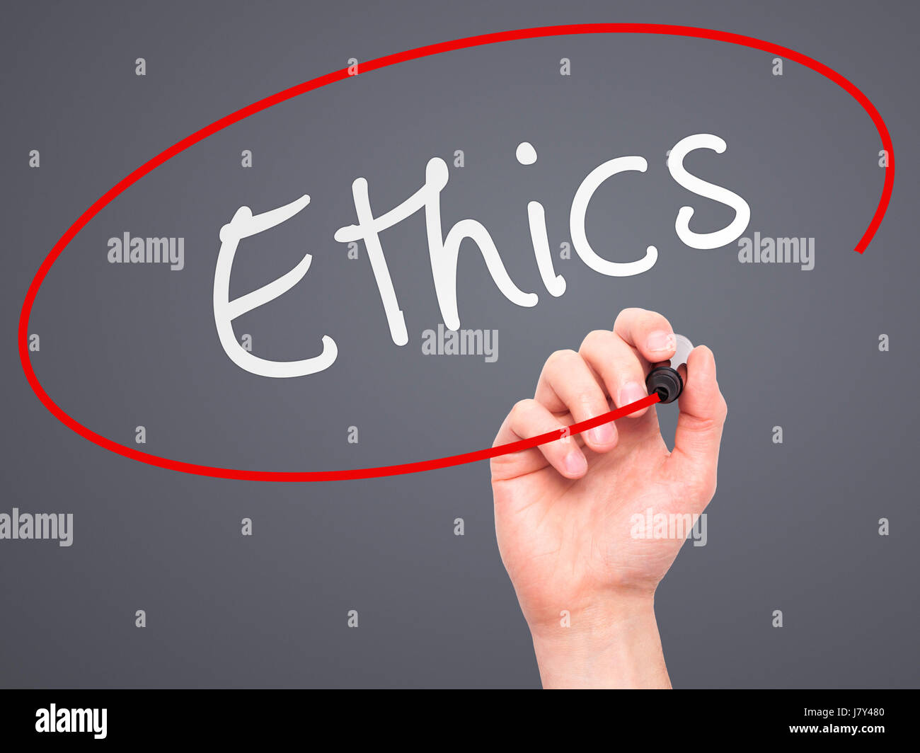 Man hand writing Ethics on visual screen. Business,help, internet, technology concept. Isolated on grey. Stock Photo - Stock Image