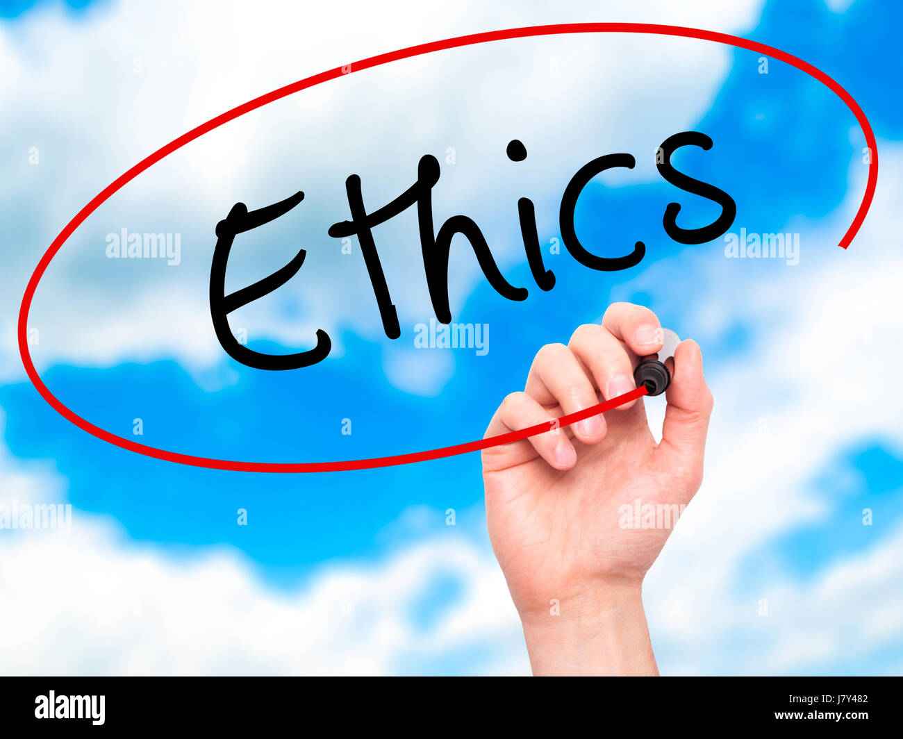Man hand writing Ethics on visual screen. Business,help, internet, technology concept. Isolated on sky. Stock Photo - Stock Image
