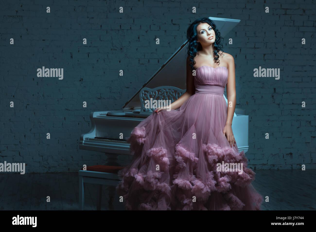 Beautiful woman posing next to a white piano. Her lush pink dress. - Stock Image