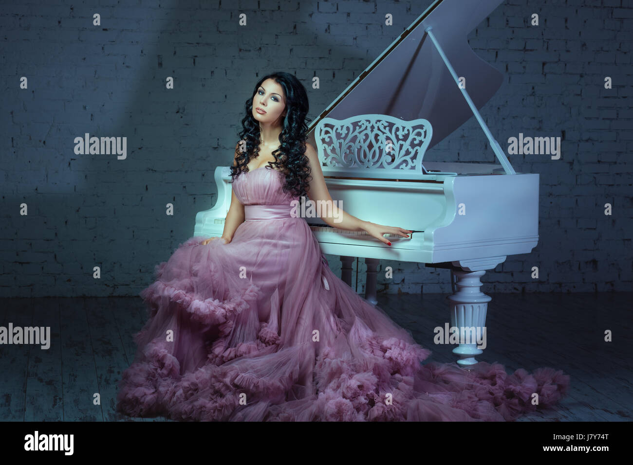In a dark room girl sitting at a white grand piano. - Stock Image