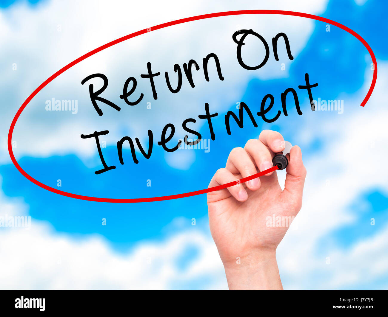 Man Hand writing Return On Investment  with black marker on visual screen. Isolated on sky. Business, technology, Stock Photo