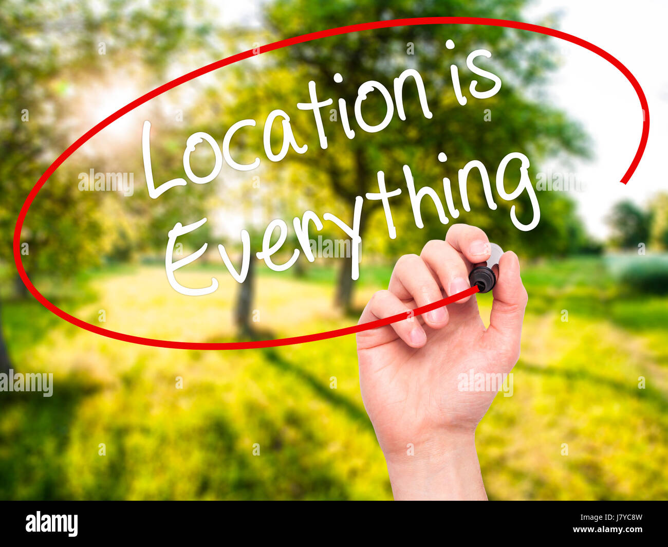 Man Hand writing Location is Everything with black marker on visual screen. Isolated on background. Business, technology, - Stock Image