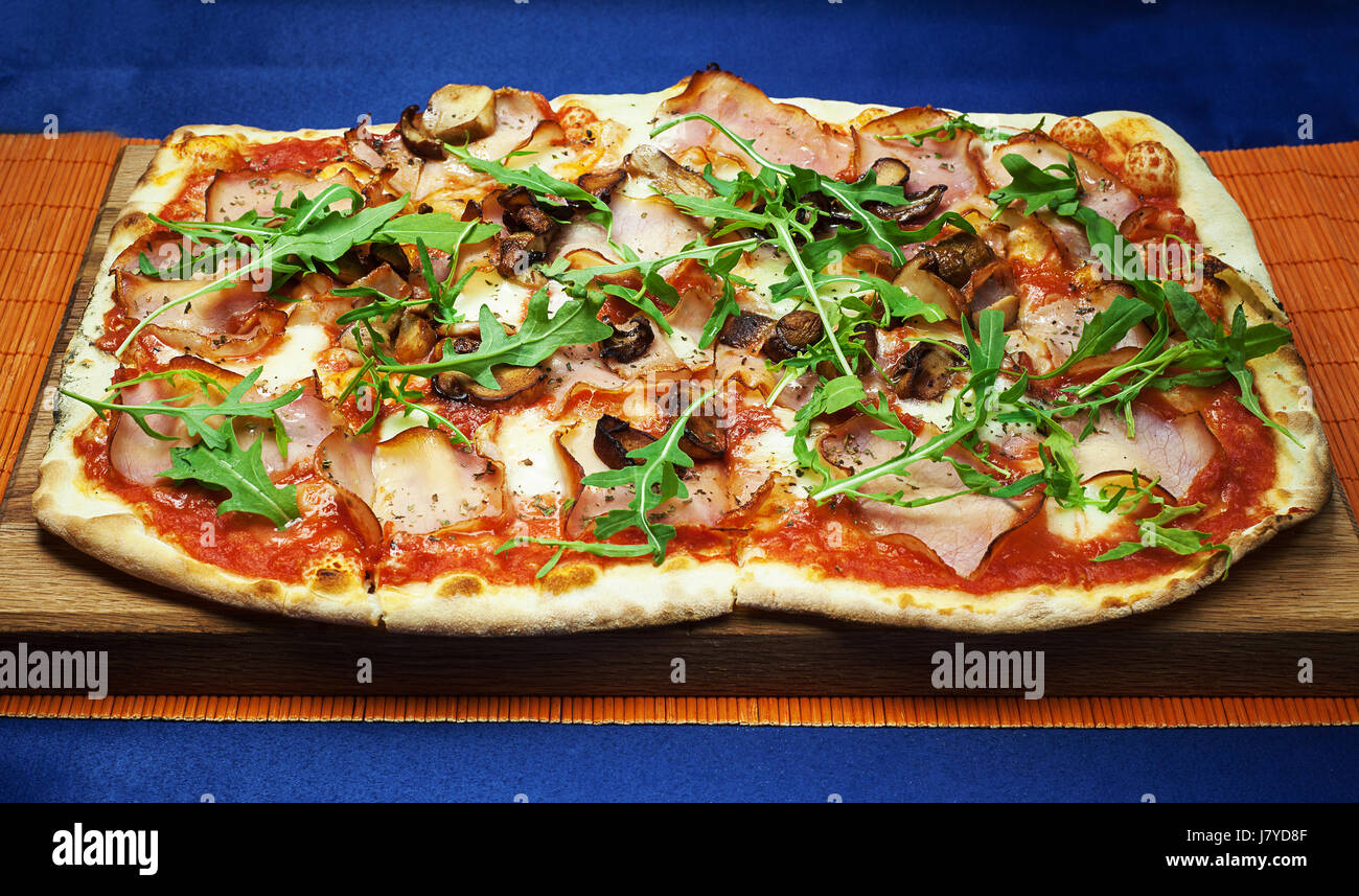 Large pizza with grilled mushrooms and smoked ham. - Stock Image