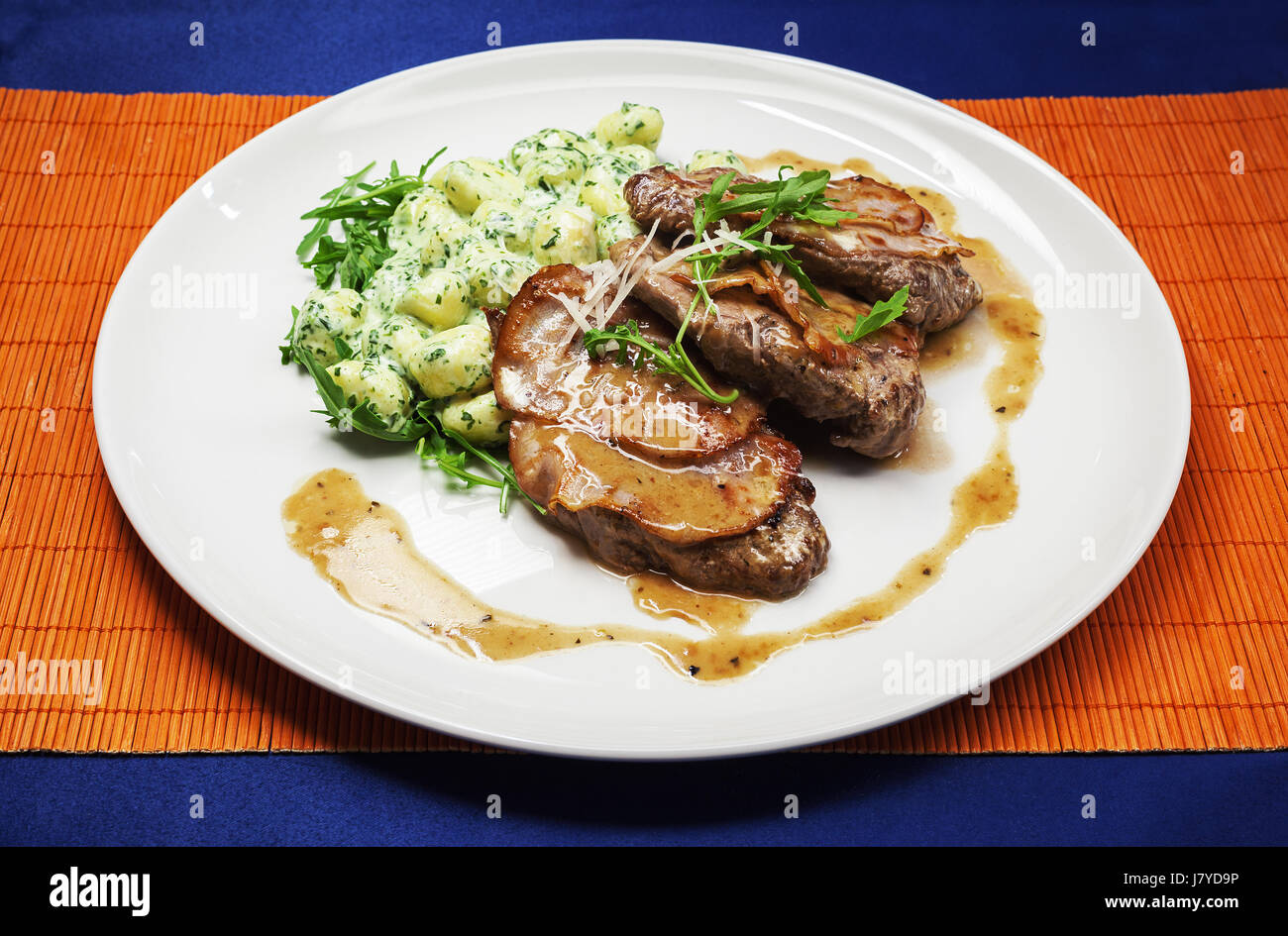 Soft steak with ham and cooked potatoes on white plate. - Stock Image