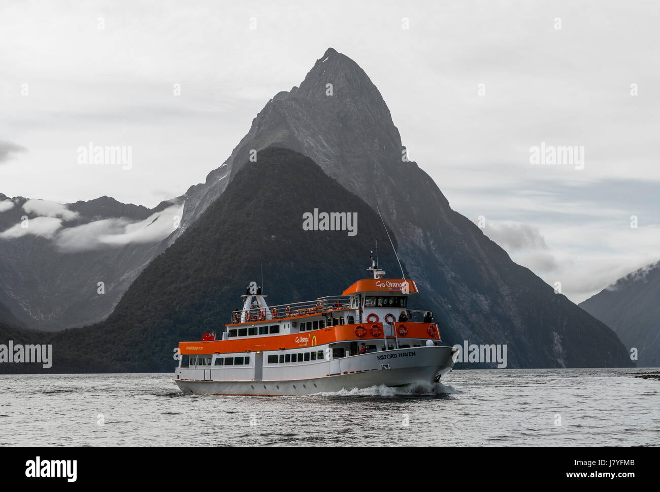 Tourist boat moving through Milford Sound, Miter Peak back, Southland, South Island, New Zealand Stock Photo