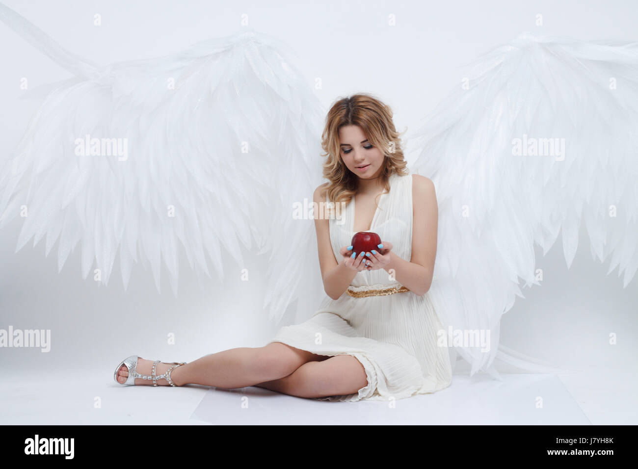 beautiful young model with big angel wings sitting in the studio and holding red apple of discord and looking at - Stock Image