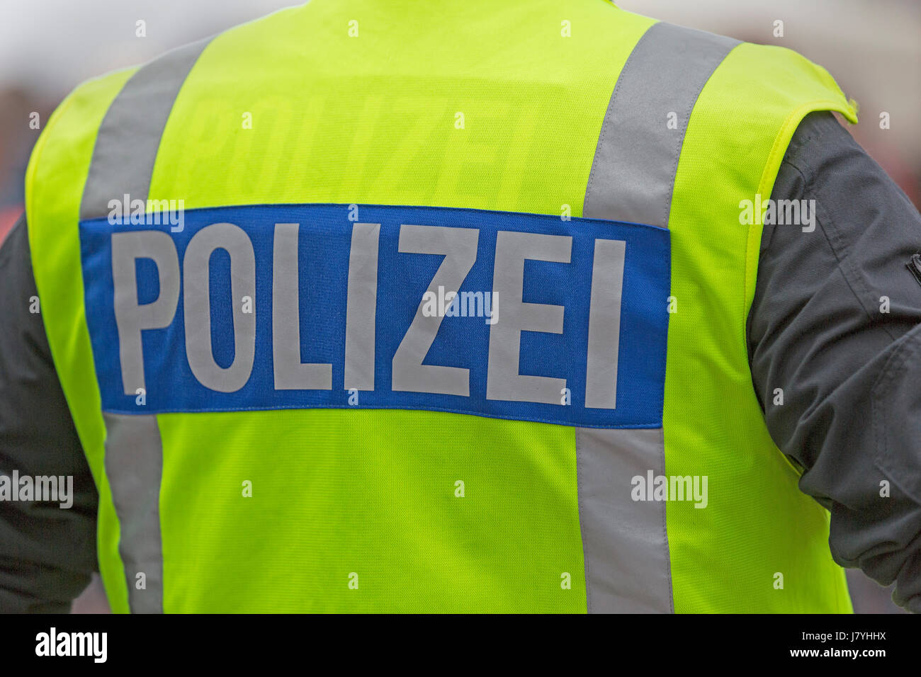 Police officer with warning vest, inscription Polizei, rear view, Germany - Stock Image