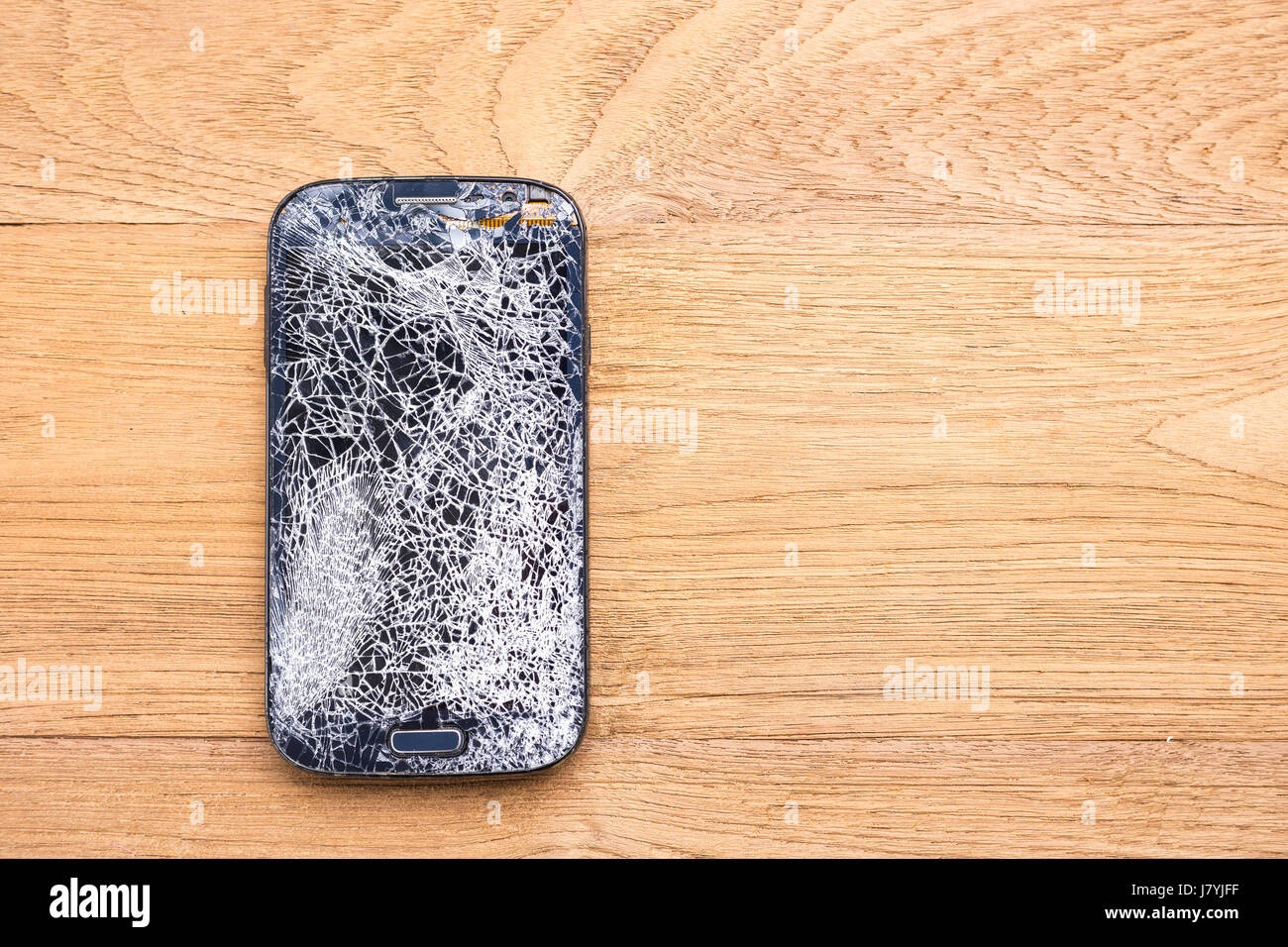 Top View Broken Of Black Smart Phone On Wooden Table Background