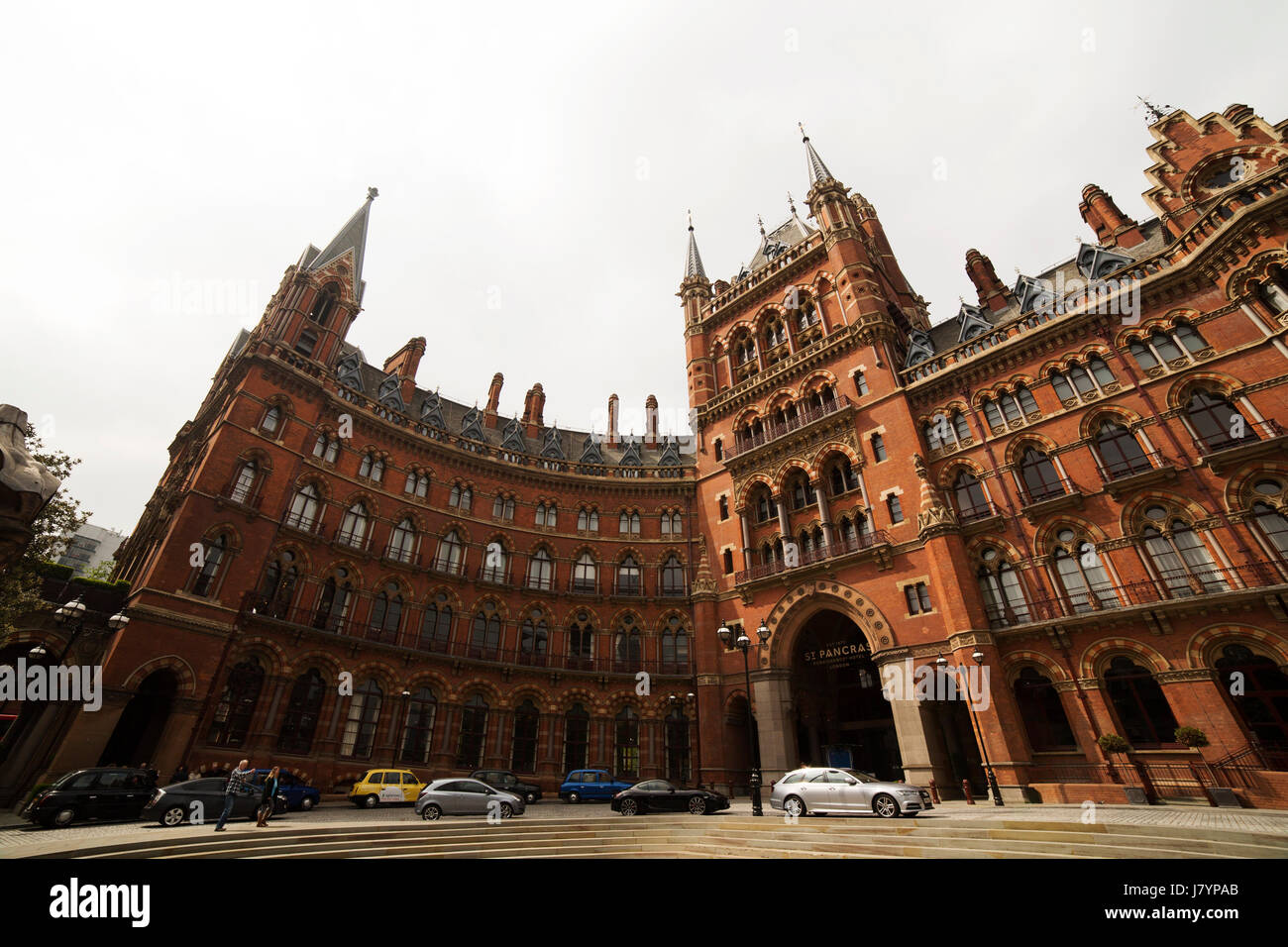 Cars park outside of the St Pancras Renaissance Hotel in London, England. The neo-Gothic building was constructed - Stock Image