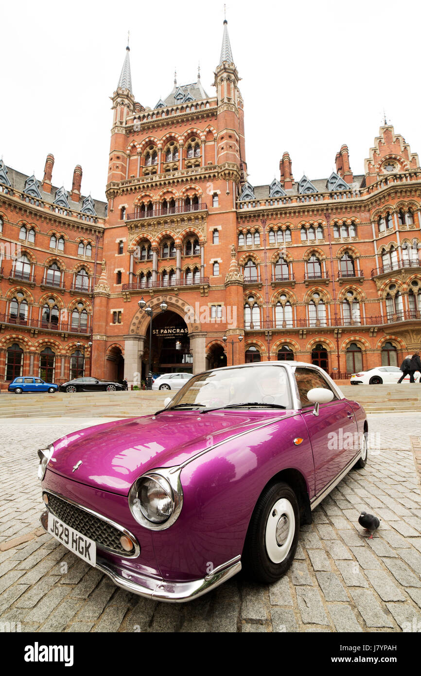 Pink sports car outside of the St Pancras Renaissance Hotel in London, England. The neo-Gothic building was constructed - Stock Image