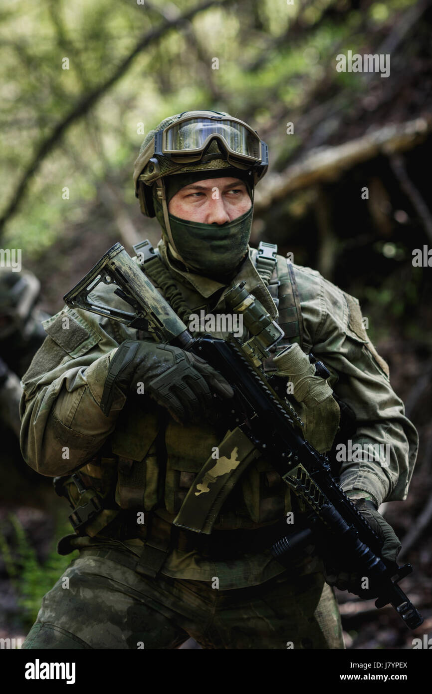 Photo of soldier in camouflage and in submachine gun at forest Stock Photo
