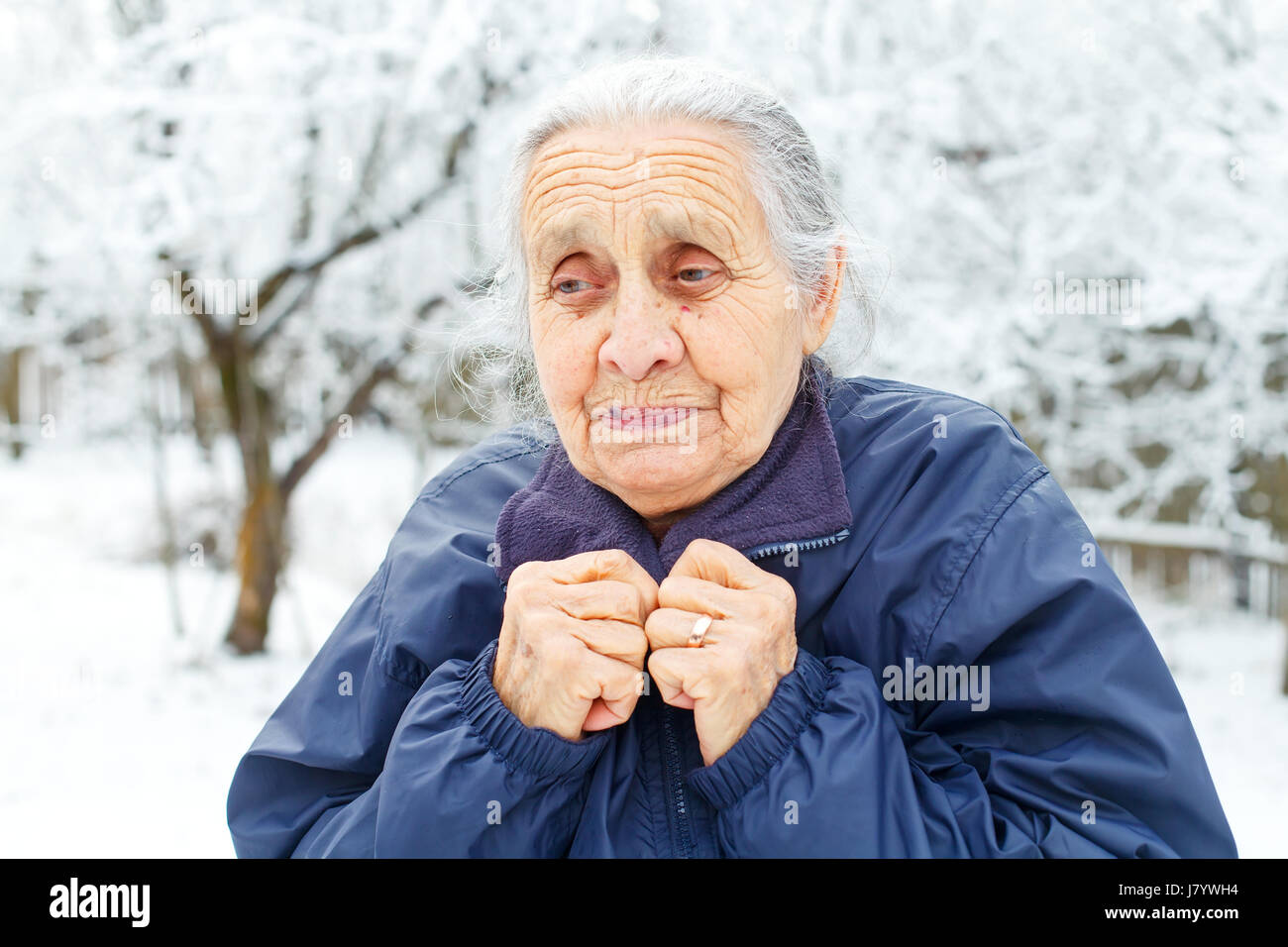 Portrait of an old lady feeling cold on wintertime - Stock Image