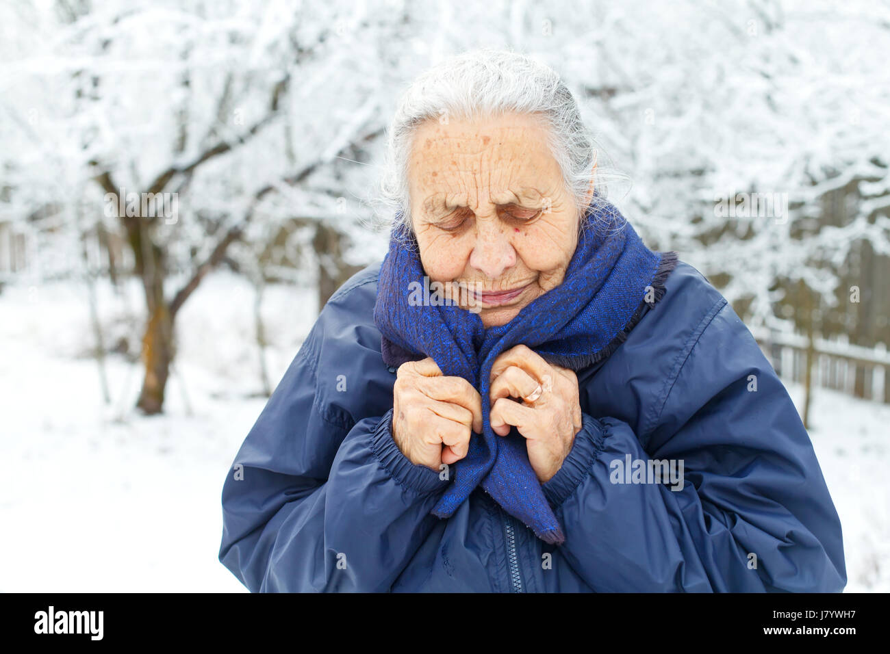 Picture of an old lady feeling cold on wintertime - Stock Image