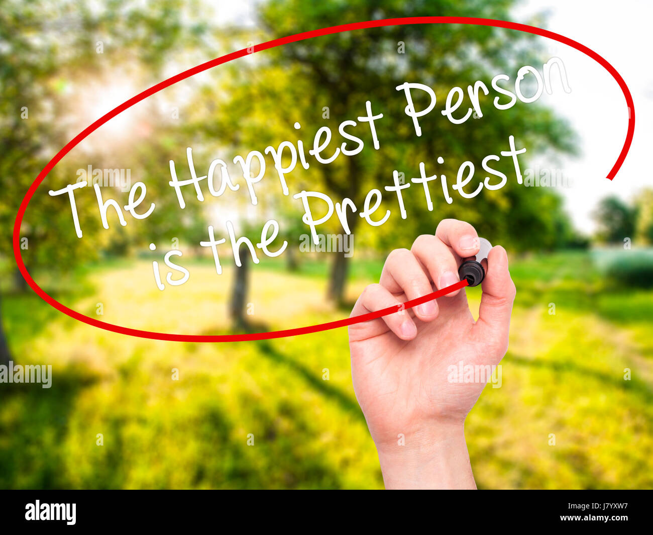 Man Hand writing The Happiest Person is the Prettiest with black marker on visual screen. Isolated on background. - Stock Image