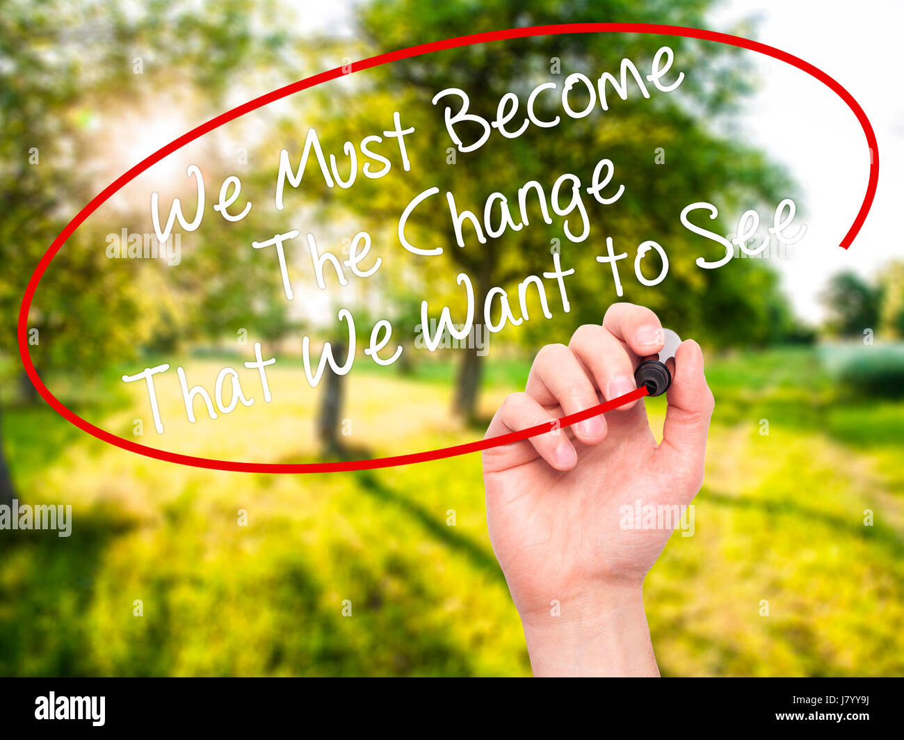 Man Hand writing We Must Become The Change That We Want to See with black marker on visual screen. Isolated on background. - Stock Image