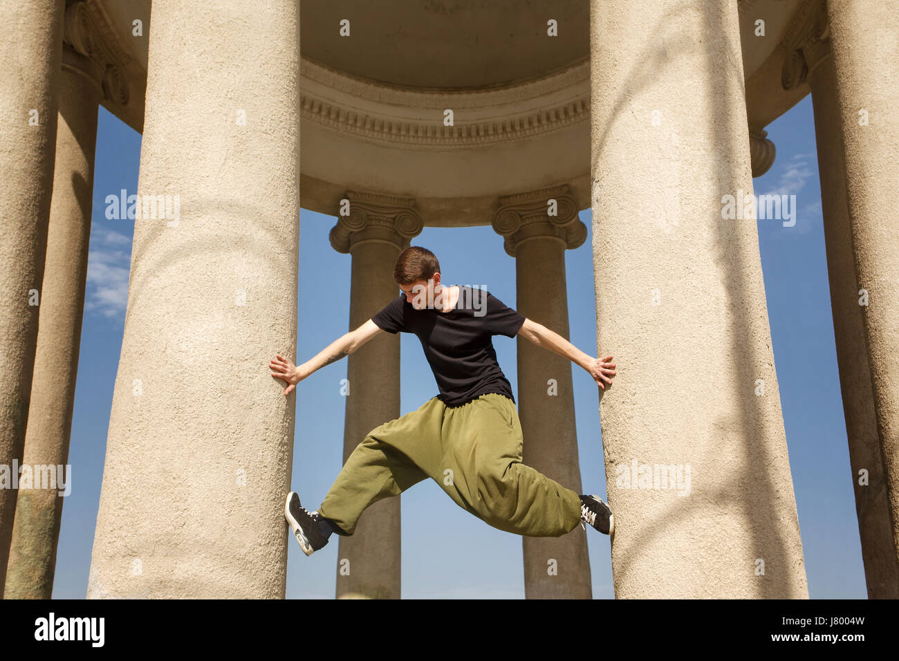 Young man climbs up honey columns. Parkour in the urban space. Sport in the city. Sport Activities outdoors. Acrobatics - Stock Image