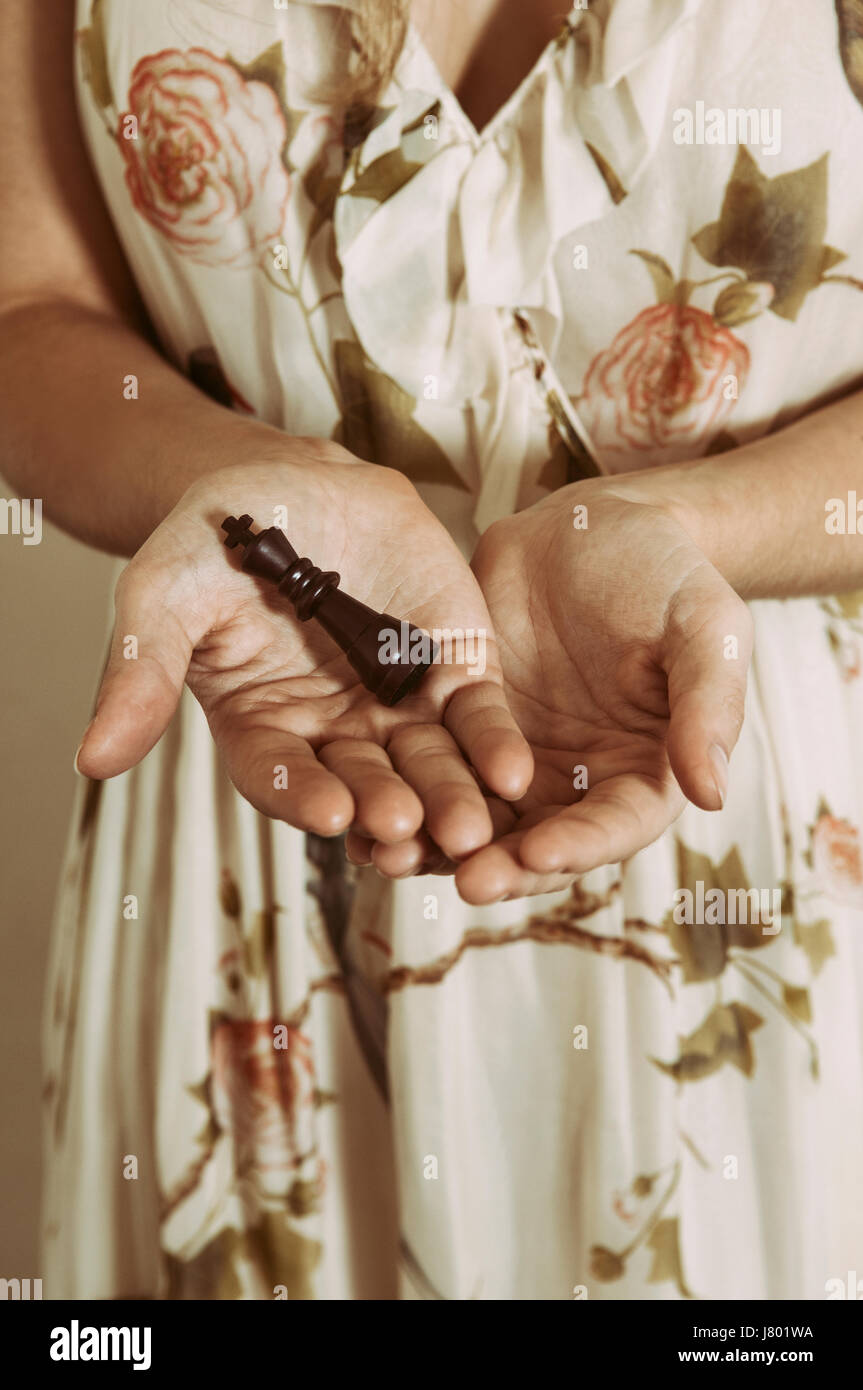 Close up of a woman's hands holding a chess king piece - Stock Image