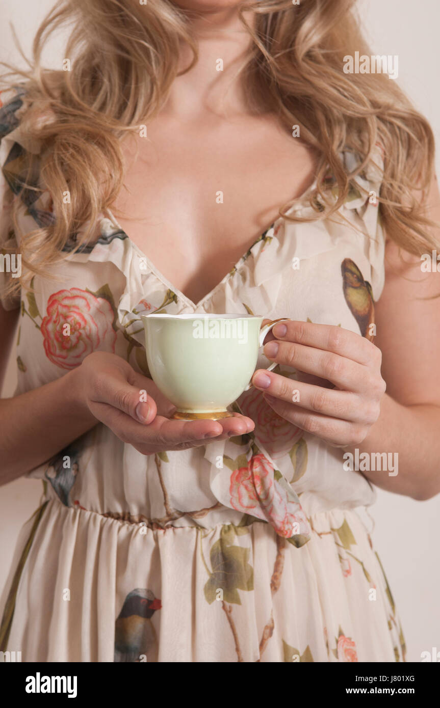 Close up of a woman holding a green teacup - Stock Image