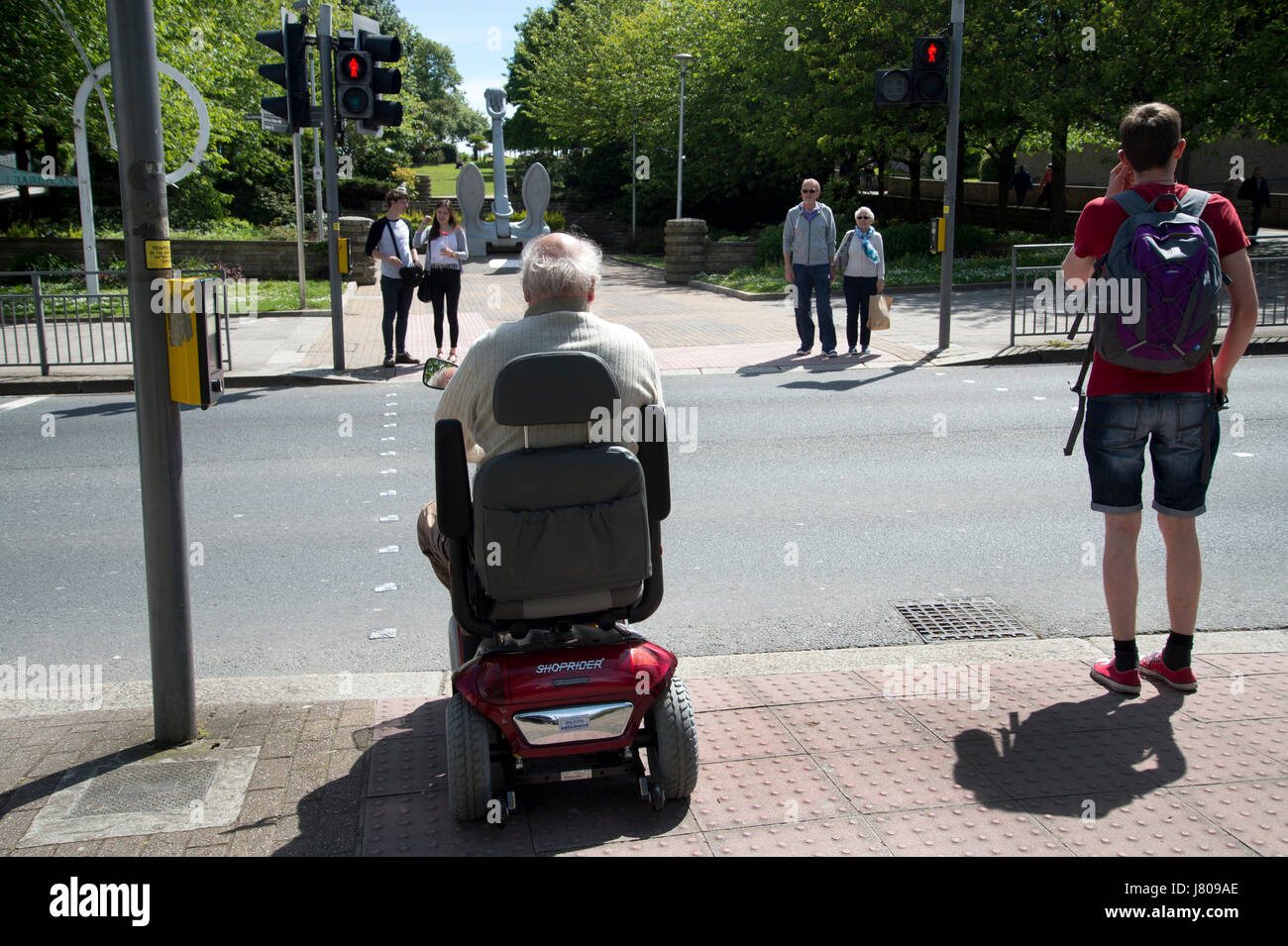 Plymouth, Devon. People including an elderly man on a disability scooter wait to cross a road - Stock Image