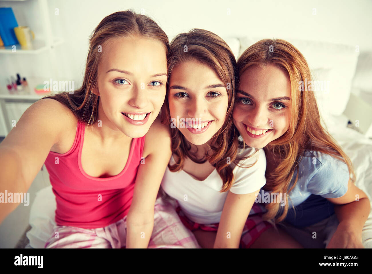 happy friends or teen girls taking selfie at home stock photo