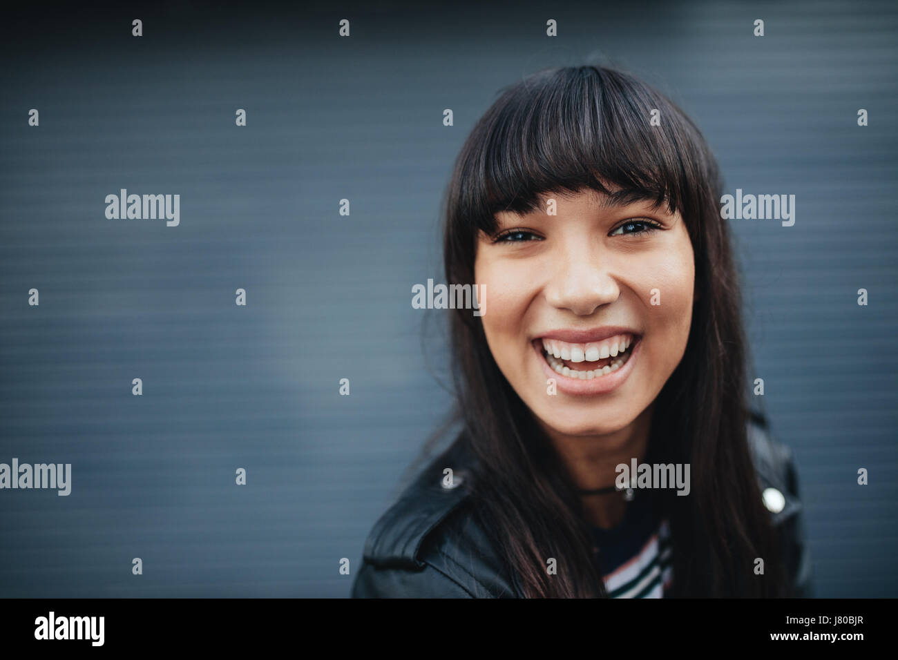 Close up portrait of young woman laughing against gray background. Beautiful hispanic female model having fun outdoors. - Stock Image