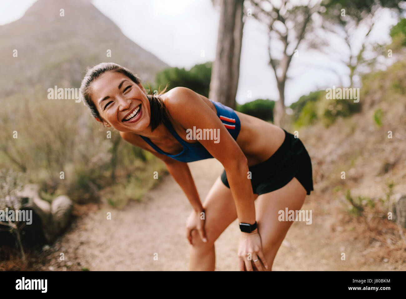 Healthy young woman standing on mountain trail with her hands on knees and laughing. Asian female runner in sportswear - Stock Image