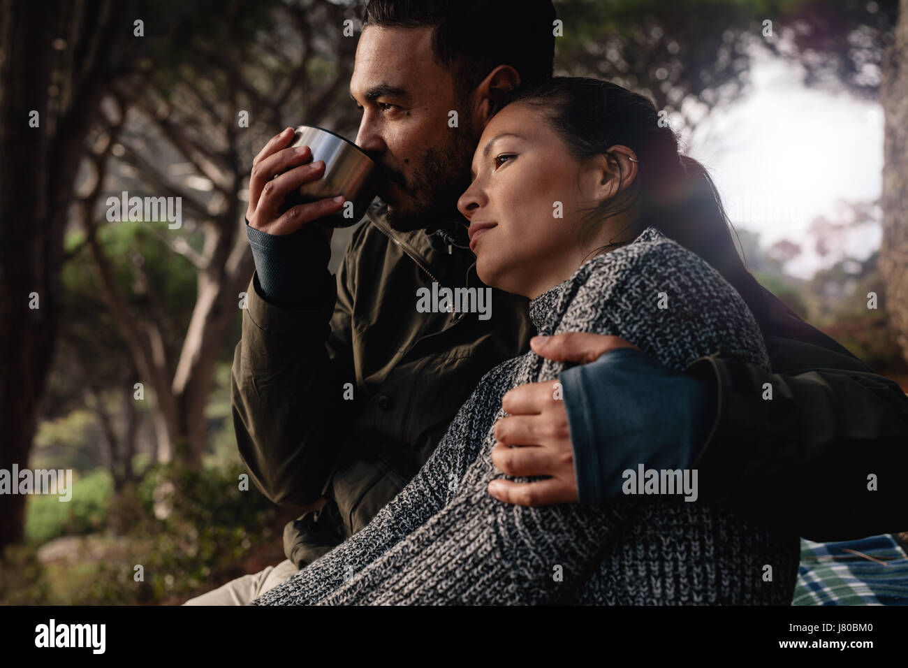 Young man and woman sitting outdoors. Relaxed young couple resting outdoors with man drinking coffee. Stock Photo