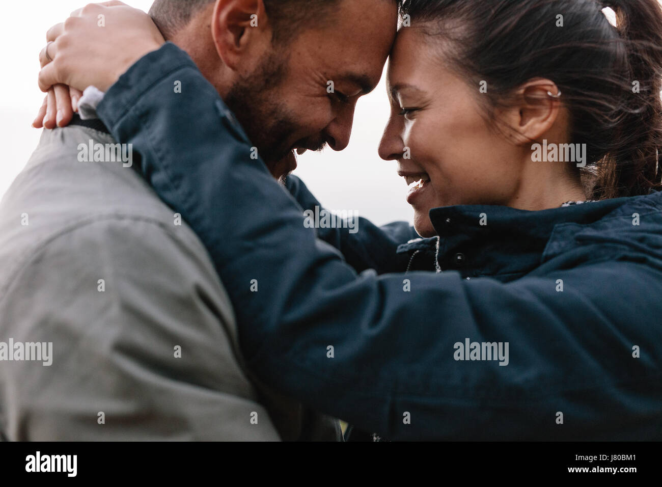 Close-up side portrait of a young couple in love to looking each other lovingly and leaning their heads on each - Stock Image