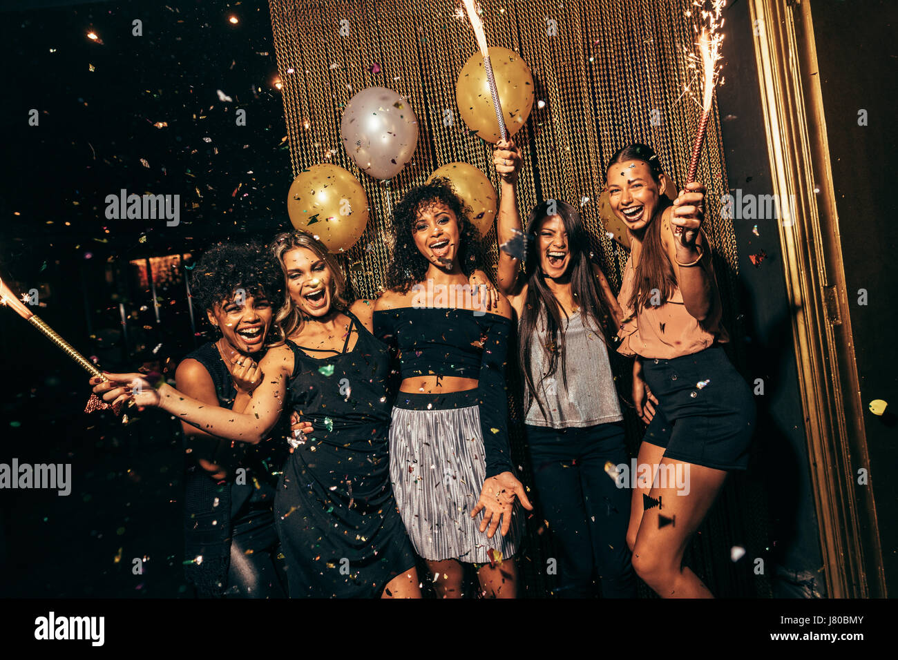 Shot of group of girls in the nightclub having a great time. Group of female friends partying in pub. - Stock Image
