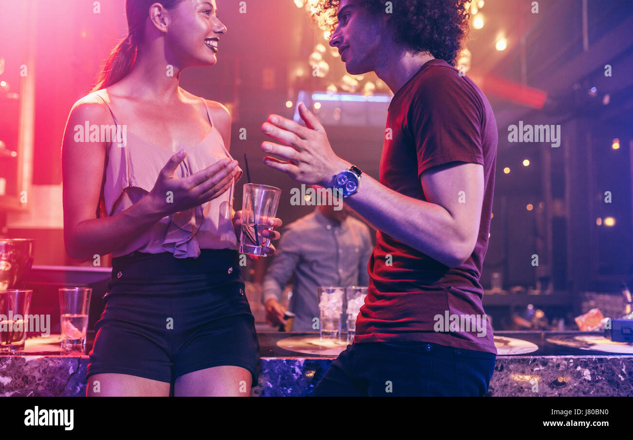 Shot of young man and woman enjoying a party. Couple talking at a nightclub. - Stock Image