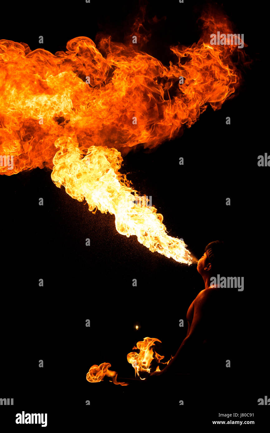 Fire breather performing in front of a crowd at night - Stock Image