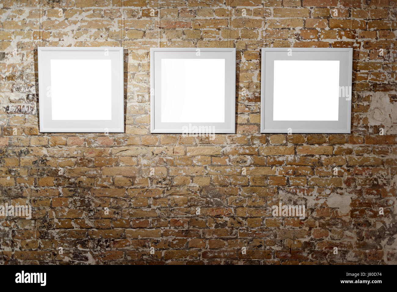 Three empty frames on light brick wall. Blank space posters or art ...