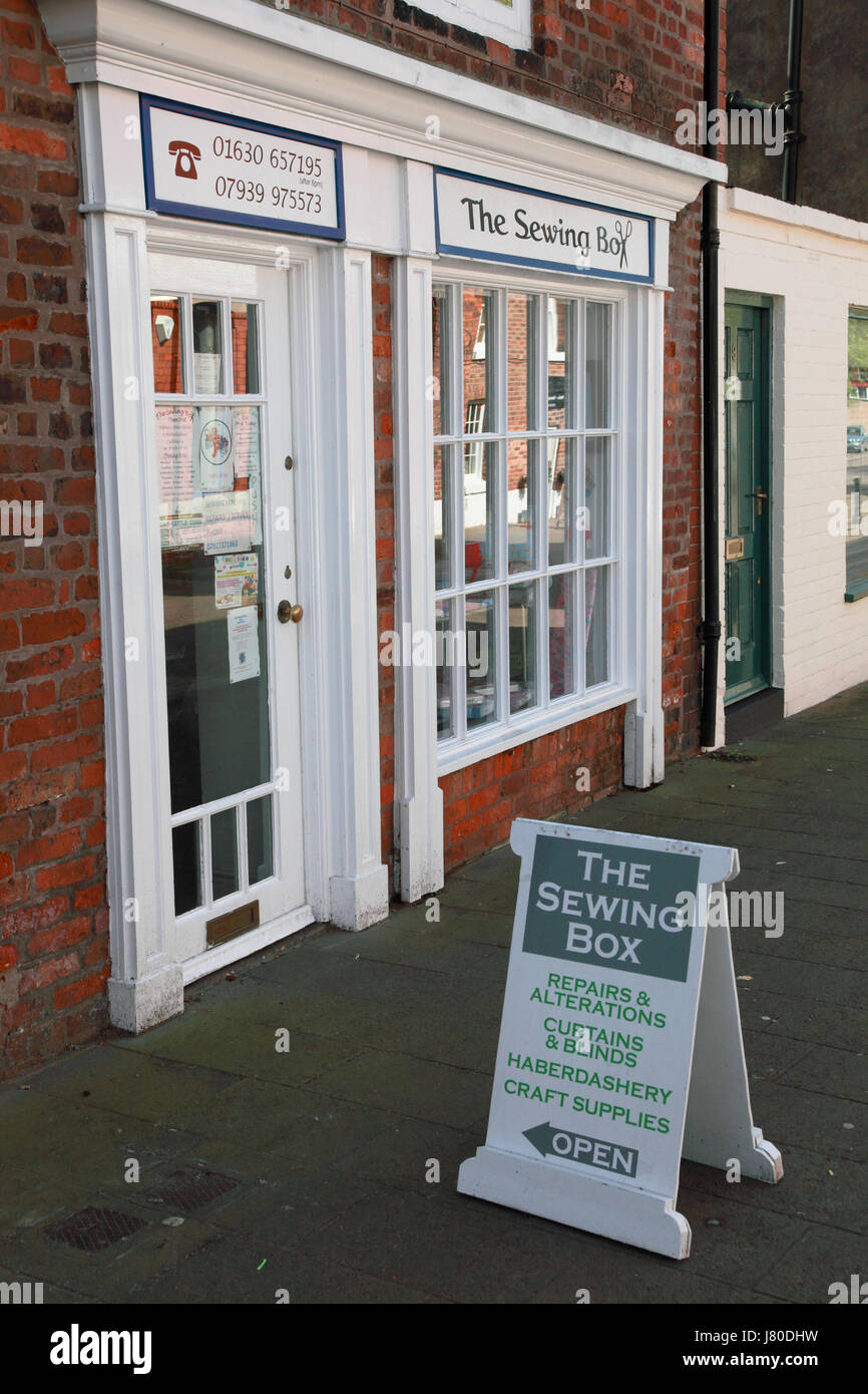 A sewing shop which repairs and alters clothes and curtains - Stock Image