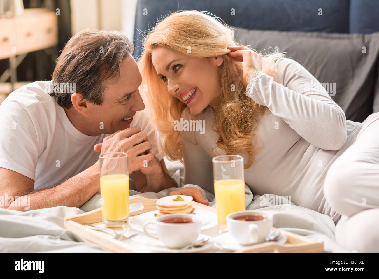 Happy middle aged couple having breakfast together in bed - Stock Image