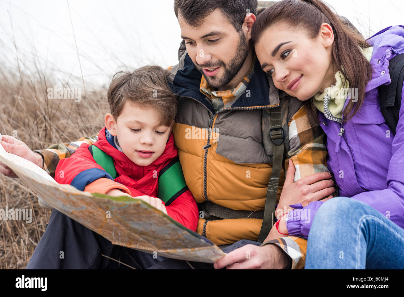Young family with backpacks sitting on grass and looking at map in countryside at autumn day - Stock Image