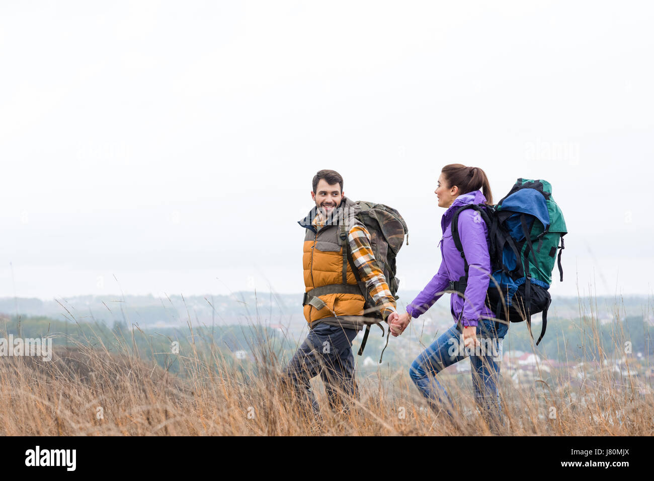 Young smiling couple with backpacks holding hands and walking in tall grass in rural area - Stock Image