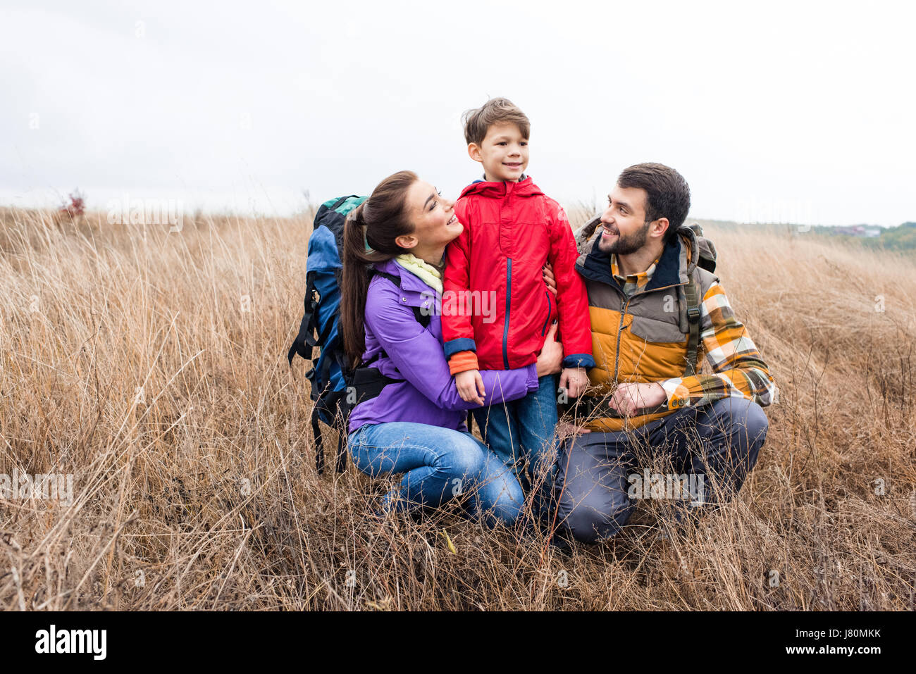 Happy family with backpacks embracing in tall dry grass and looking away at cloudy autumn day - Stock Image