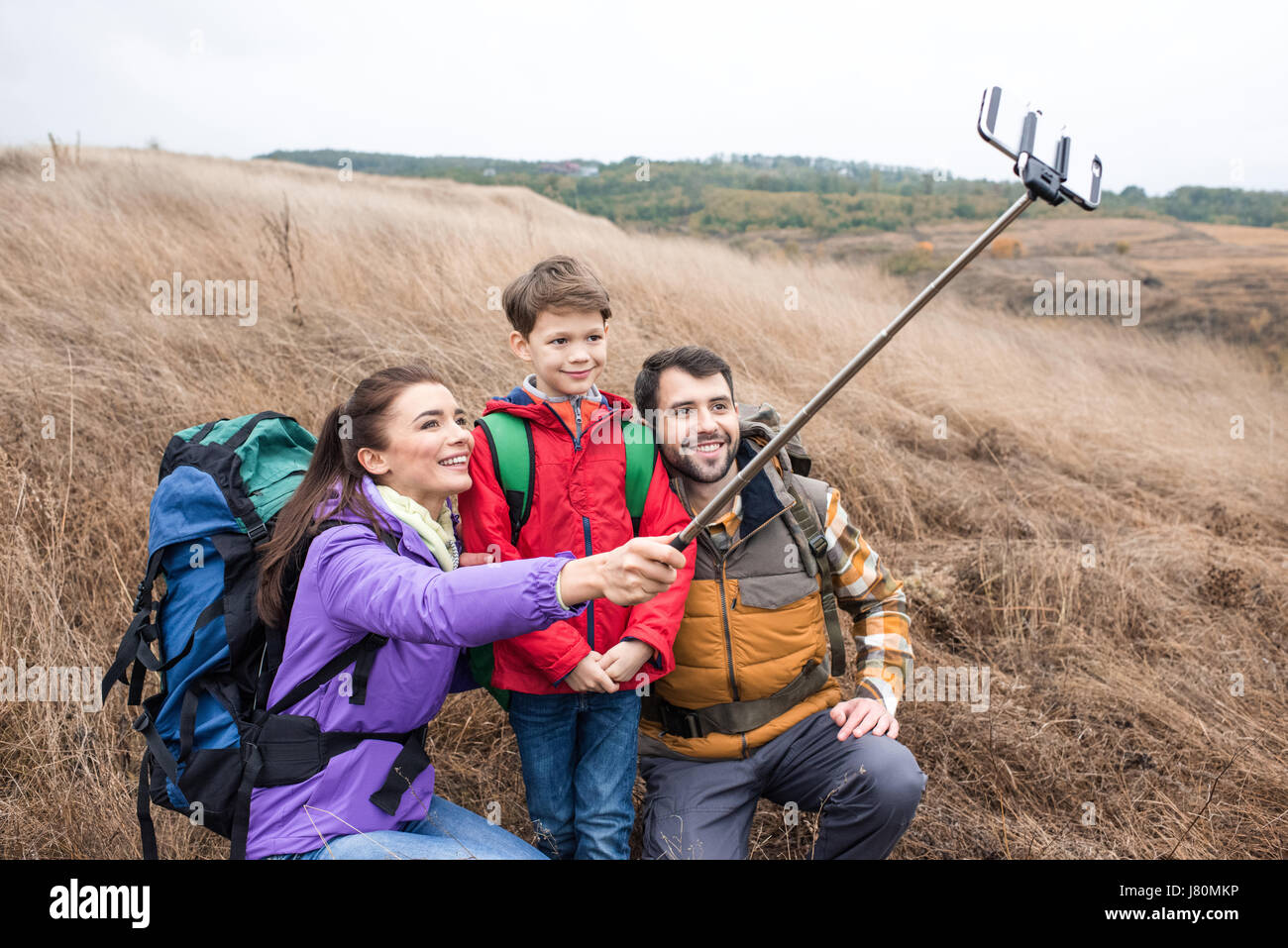 Happy family with backpacks in tall dry grass taking selfie in rural area - Stock Image