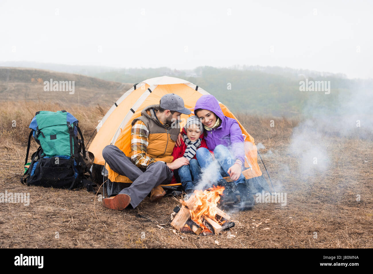 Happy family sitting near tent and looking at burning fire at cloudy autumn day - Stock Image