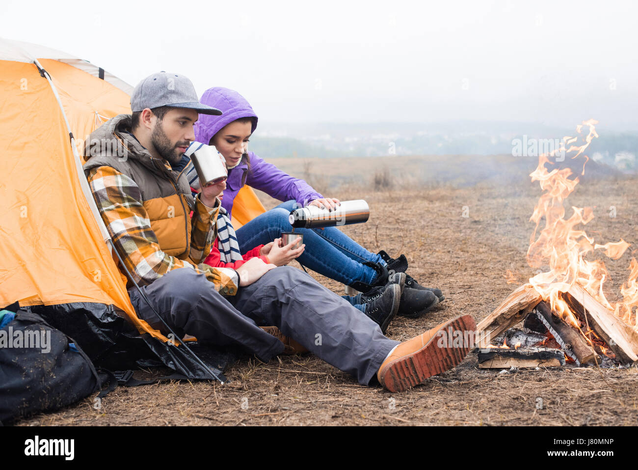 Family with one child sitting near tent and drinking hot tea from thermos while resting near burning fire in countryside - Stock Image