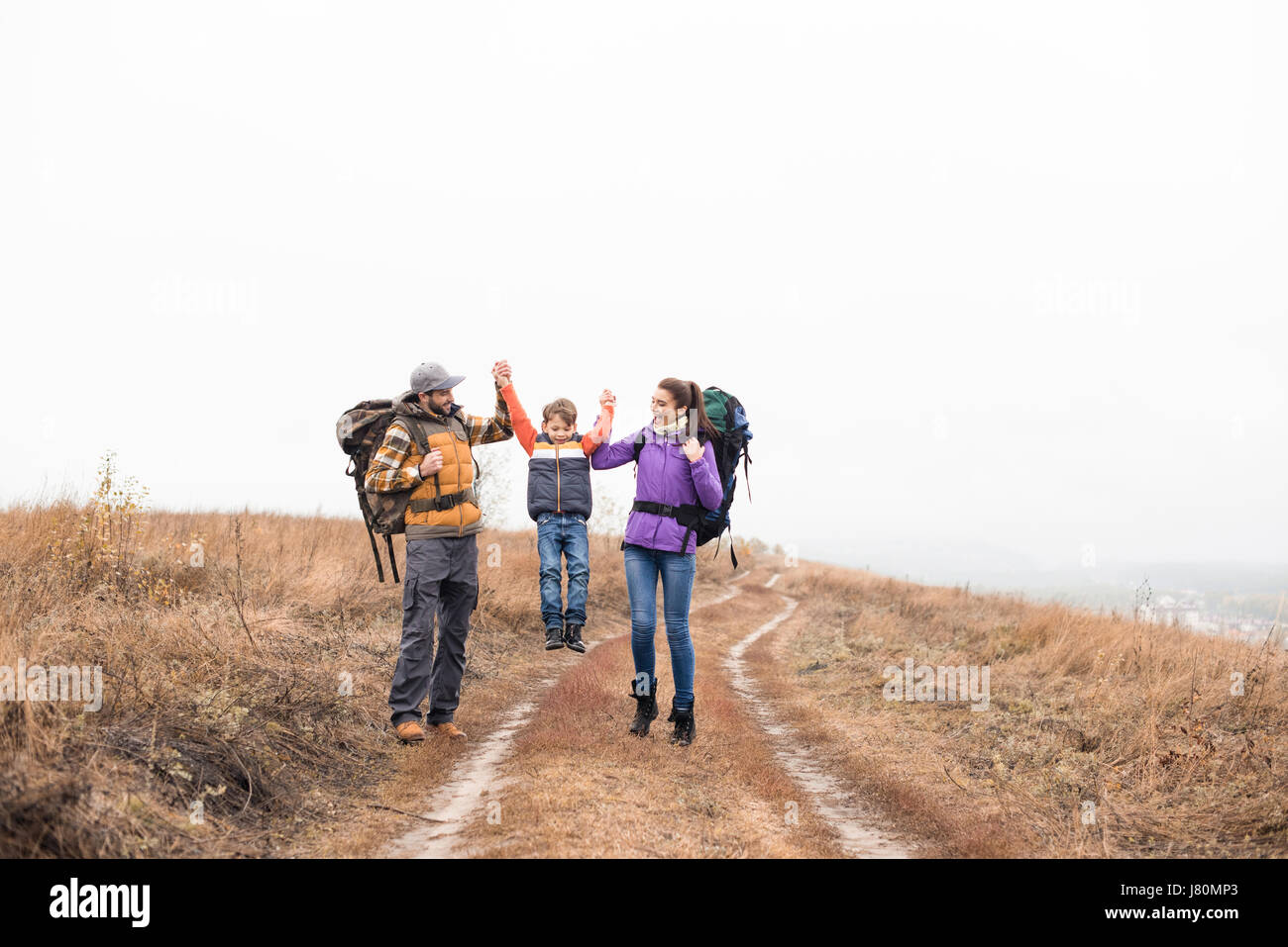 Happy young family with backpacks holding hands and walking on rural path at cloudy autumn day - Stock Image