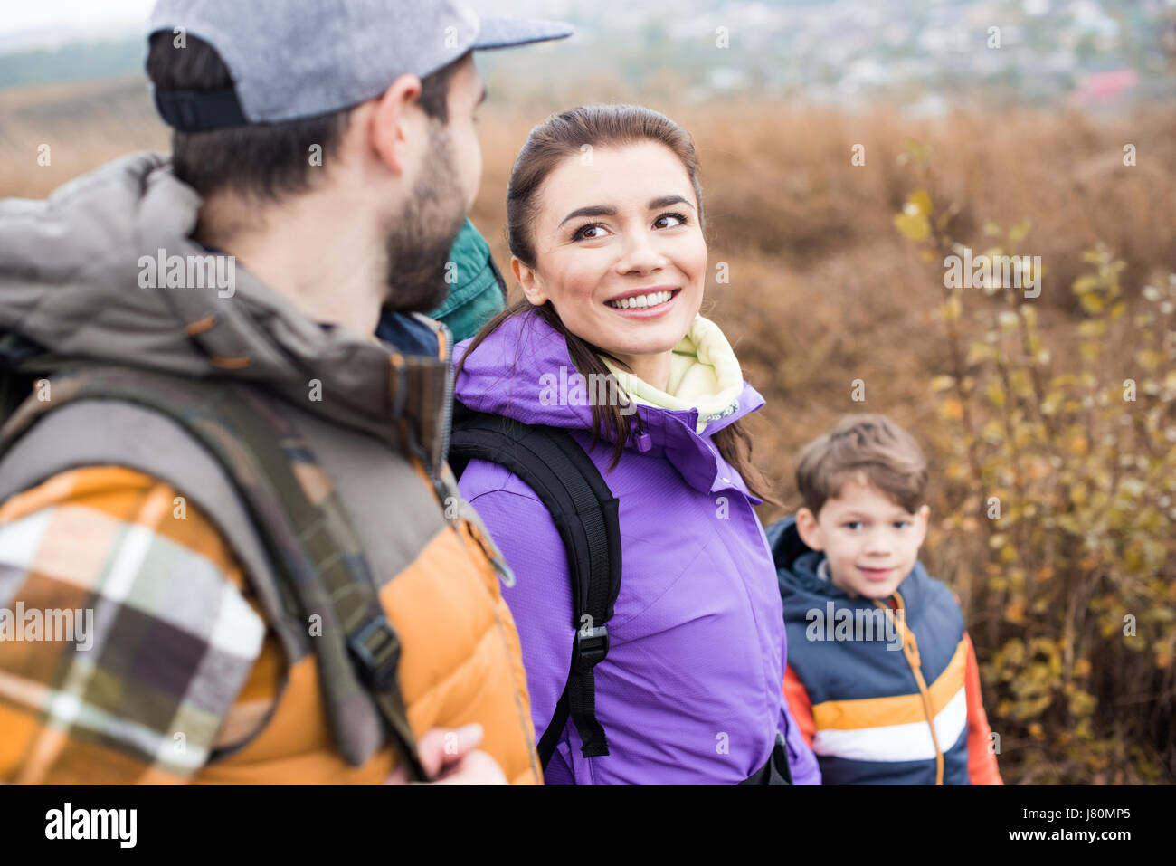 Happy family with backpacks holding hands and looking at each other - Stock Image