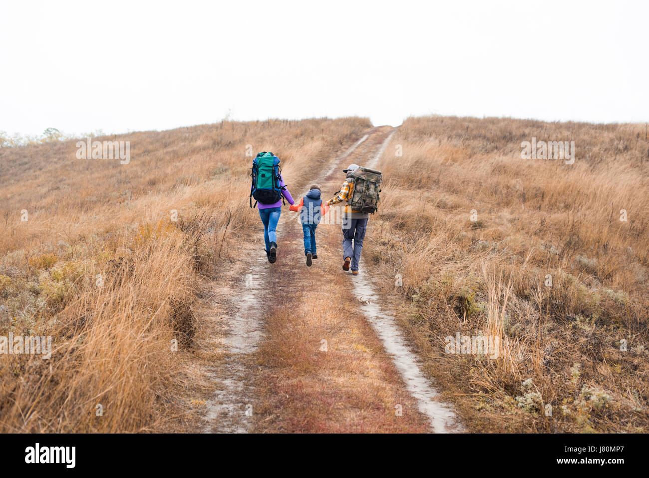 Back view of happy young family with backpacks holding hands and running on rural path at cloudy autumn day - Stock Image