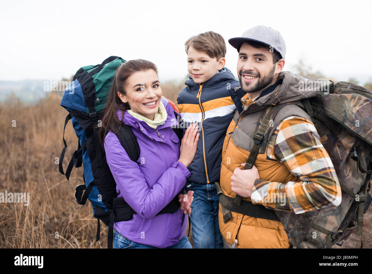 Close-up portrait of smiling family with backpacks standing embracing on rural path - Stock Image
