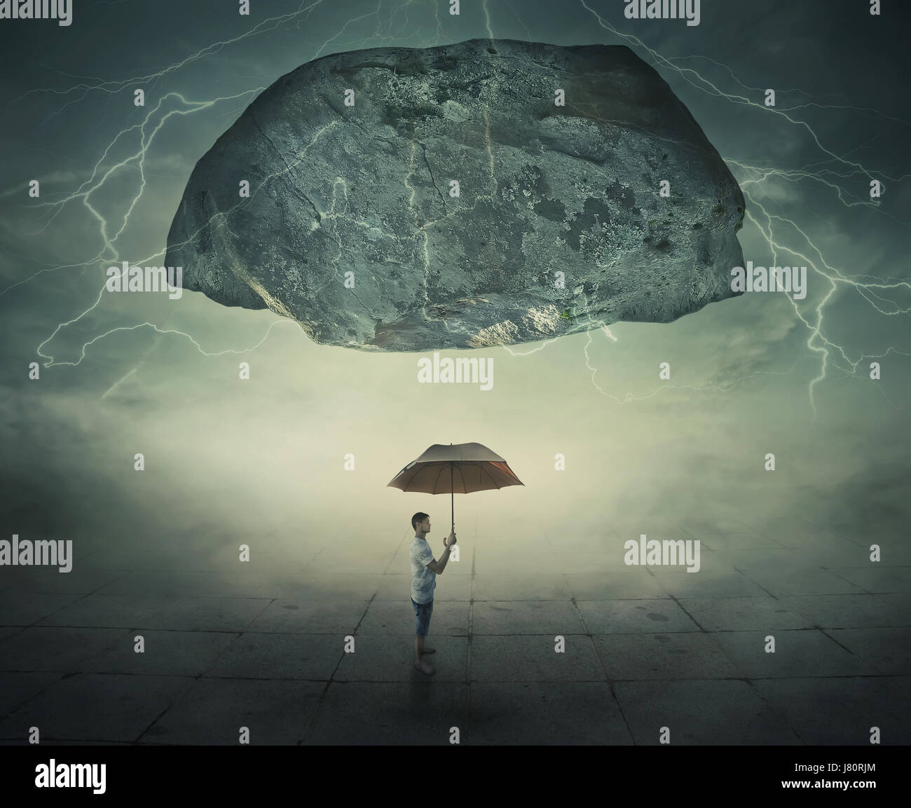 Surrealistic image as a man stand in a foggy street under a huge levitating rock, holding an umbrella in hand as - Stock Image